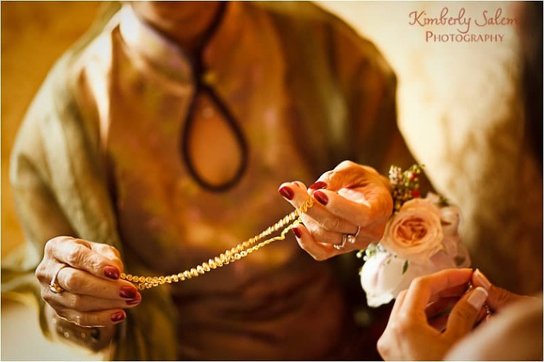 mother giving bride necklace at tea ceremony