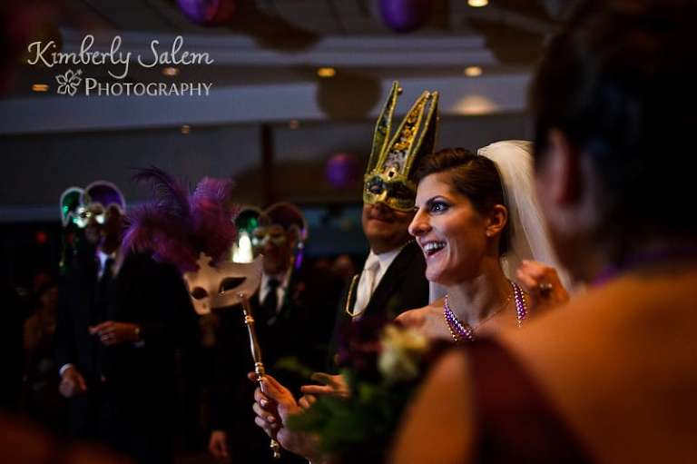 the king (groom) and queen (bride) enter their party with masks on