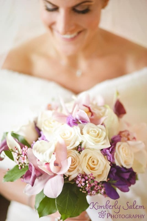 Bride holding purple and white bouquet