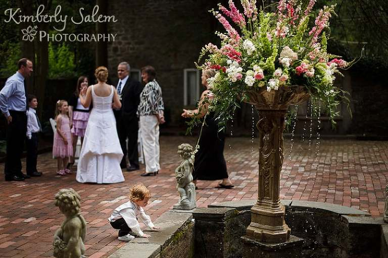 Ring bearer checks out the wishing well while the bride chats in the background