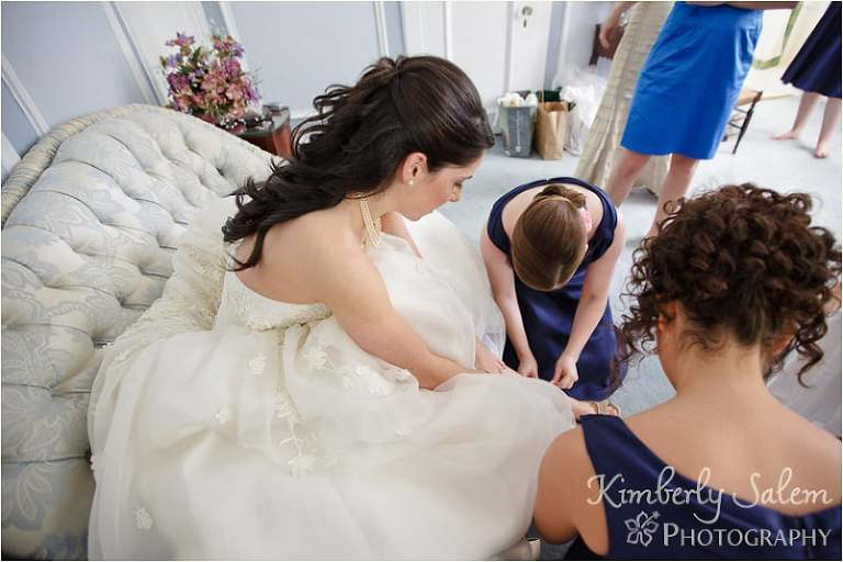 bridesmaids help bride put on her shoes