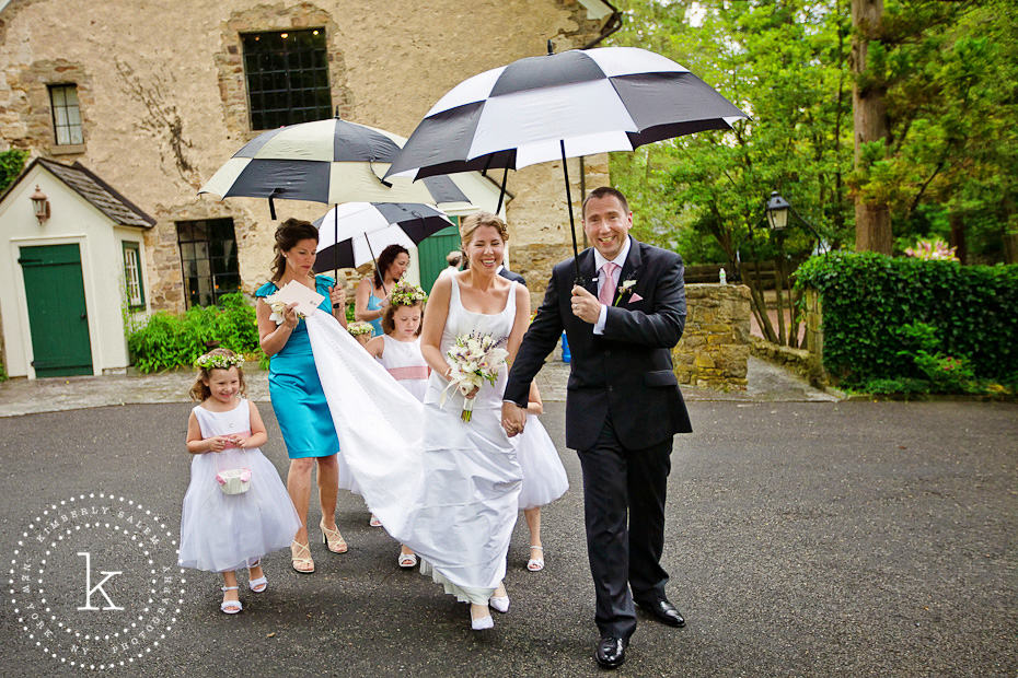 bride and groom with umbrellas and flower girls