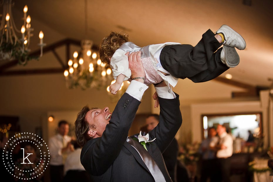 happy ring bearer being tossed in the air by his father