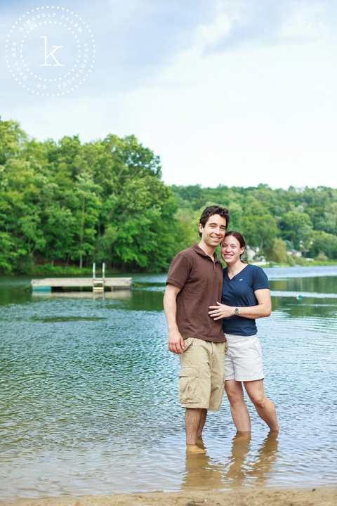 engaged couple standing in lake