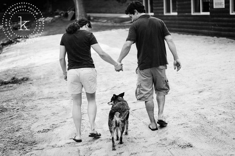engaged couple hand in hand, with dog