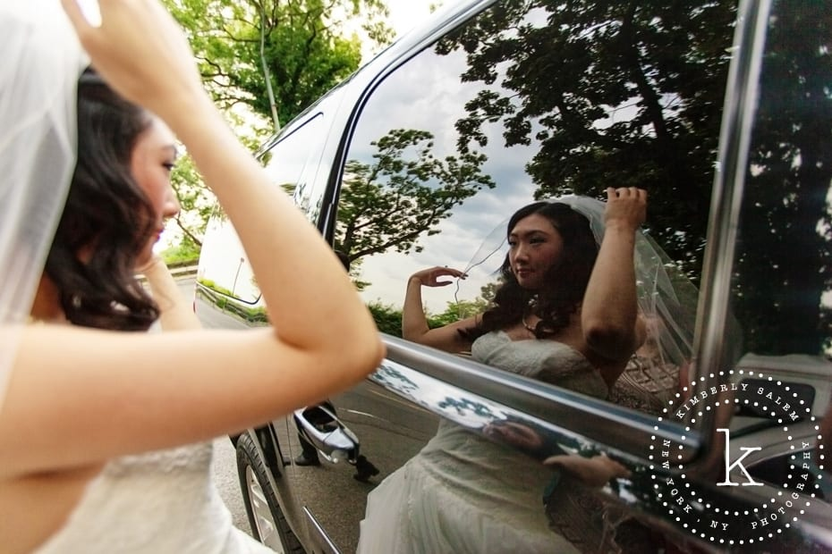 bride fixing her veil in car reflection