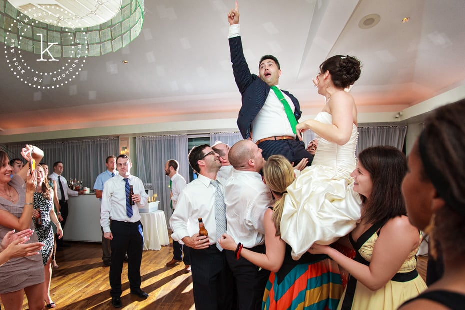 Bride and groom being lifted up at reception