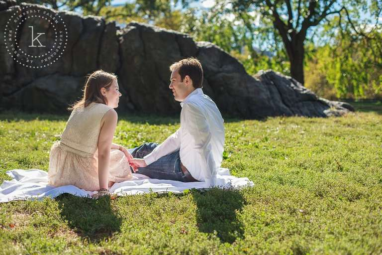 engaged couple sitting by a rock in central park