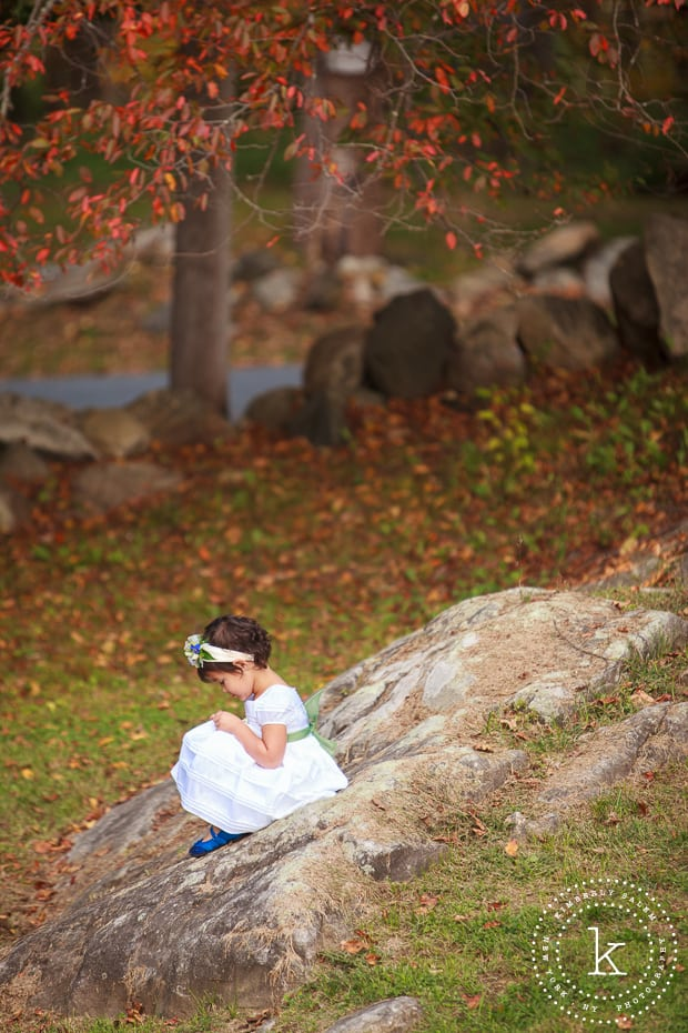 Adorable flower girl sitting on a rock