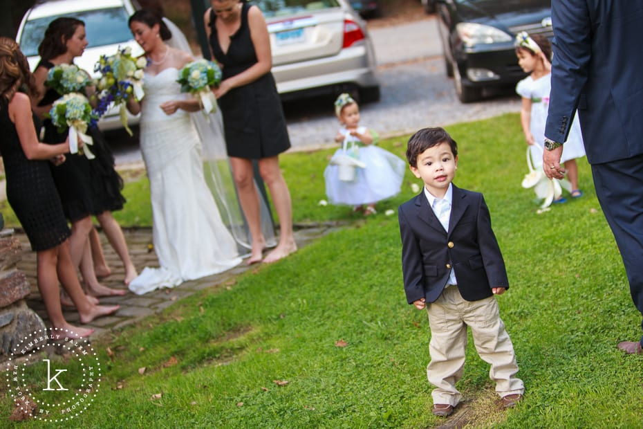 Ring bearer with bride, bridesmaids and flower girls in background
