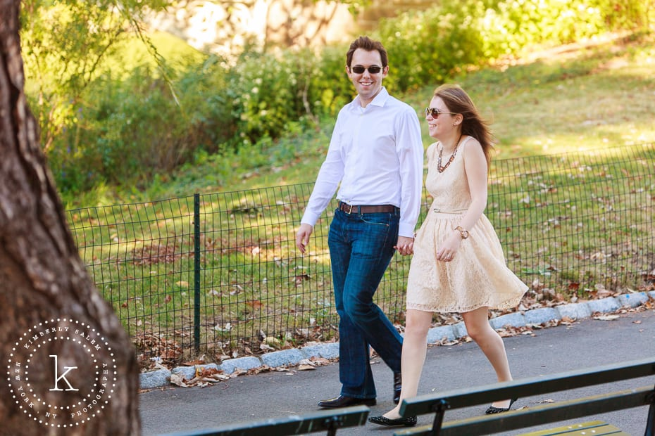 engaged couple wearing sunglasses and walking in central park