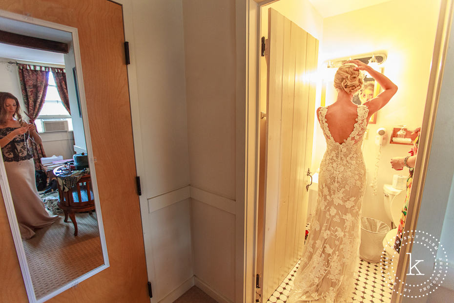 Bride fixing her hair, bridesmaid in the outer room