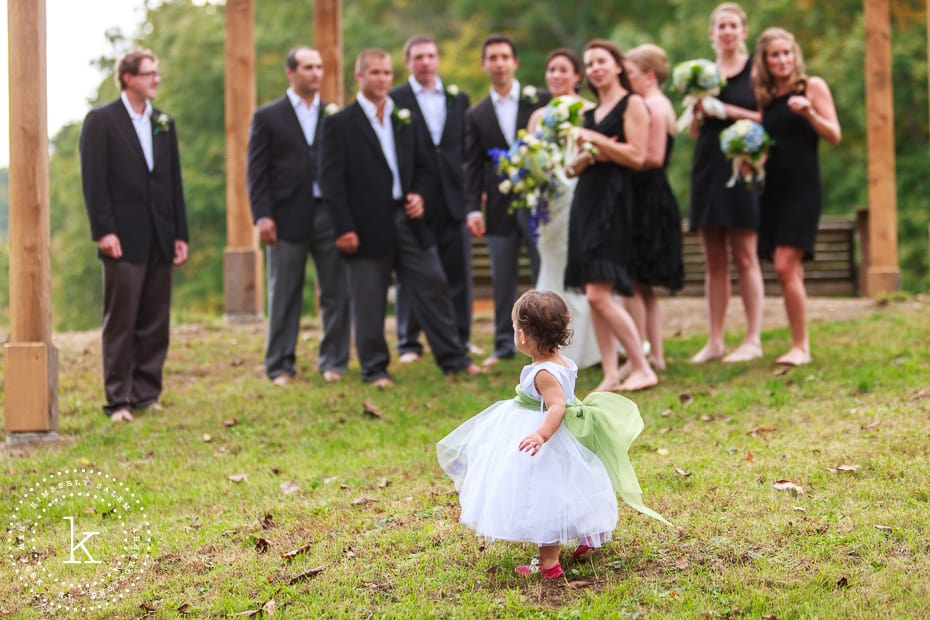 Flower girl looks back at bridal party