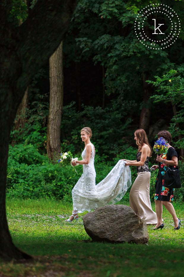 Bride walking towards the aisle with attendants - outdoor wedding