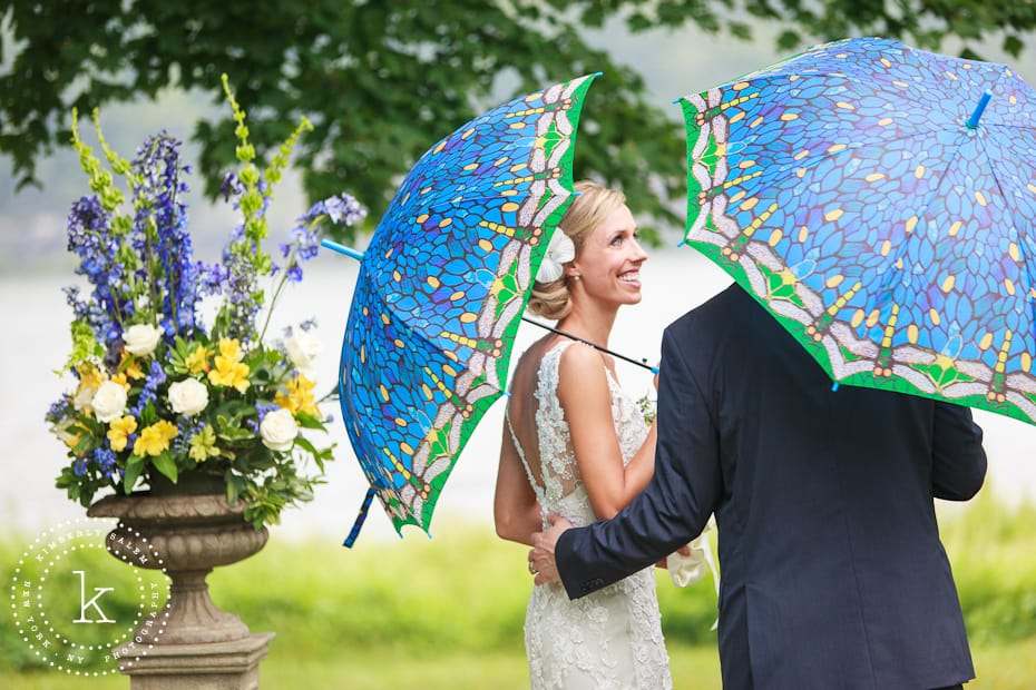 Bride looks at groom under blue umbrellas