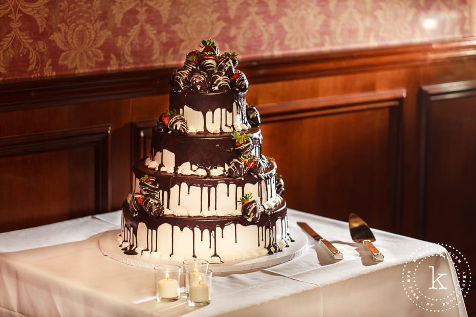 wedding cake with chocolate covered strawberries on top