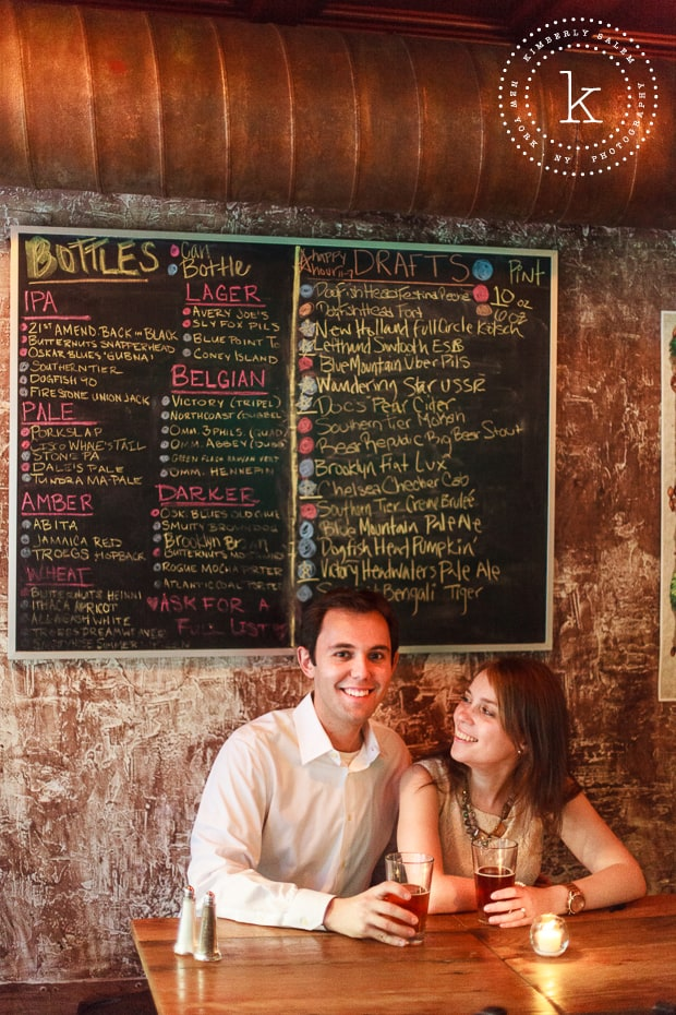 engaged couple by the beer menu at The Stag's Head in NYC