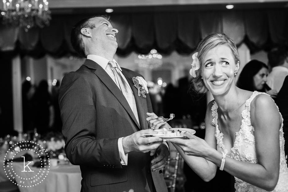 Cake cutting at wedding - laughing bride and groom