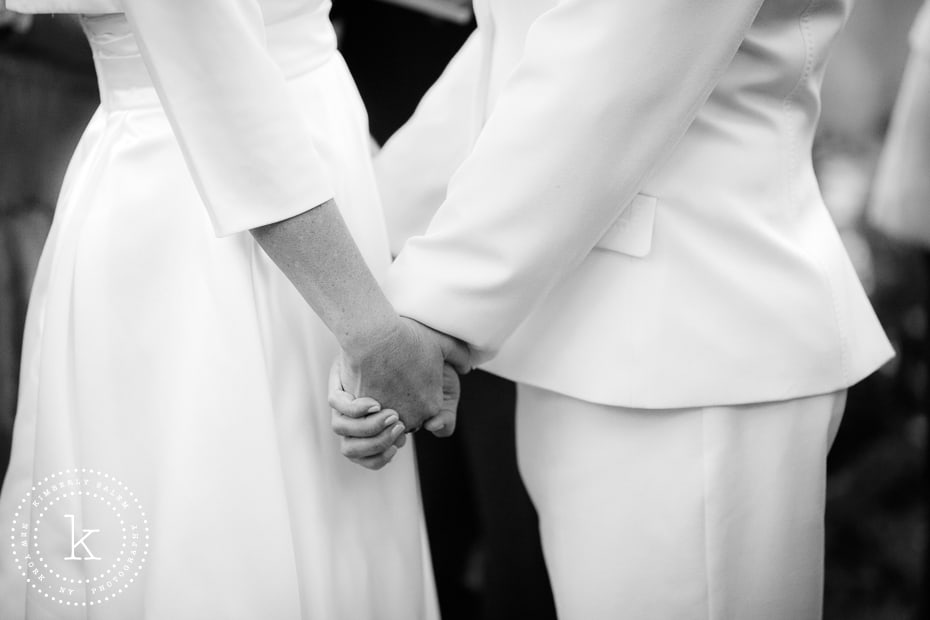 closeup of brides holding hands