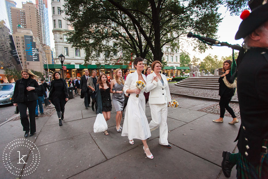brides walk behind two bagpipers along the streets of Manhattan