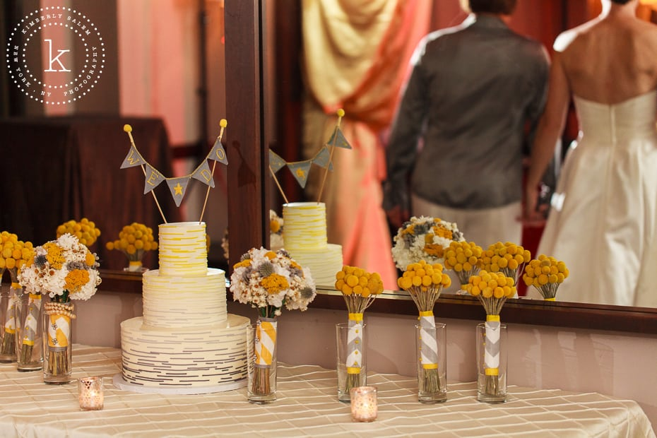 wedding cake with reflection of brides holding hands