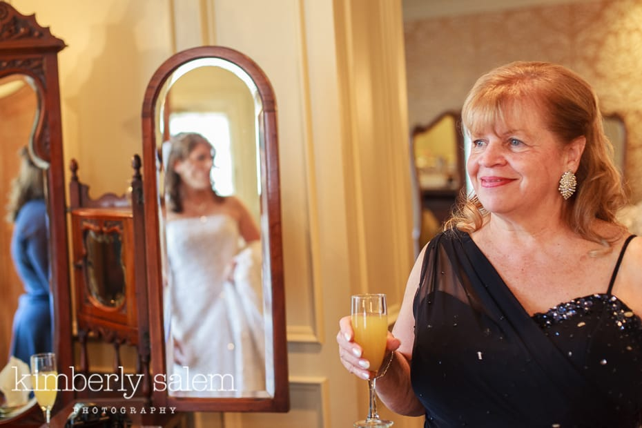mother of the bride looking on as bride gets ready