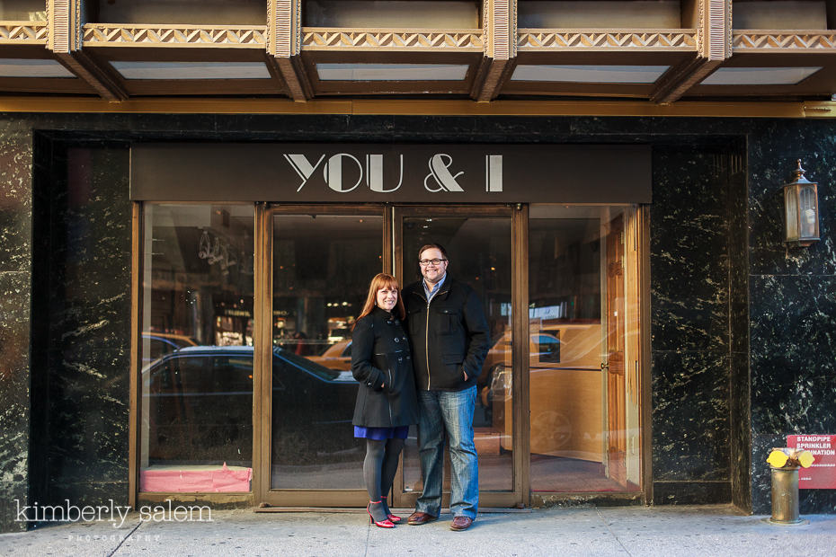 "engaged couple in front of ""You & I"" on building in NYC"
