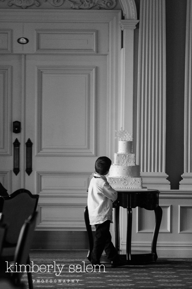 young boy contemplates wedding cake