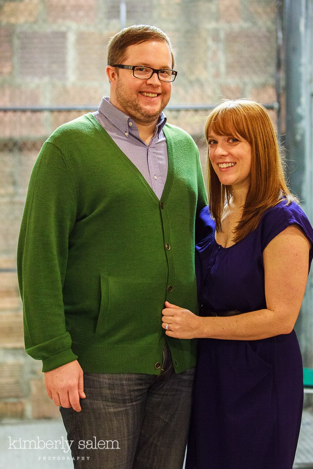 engaged couple with brick and chain link background