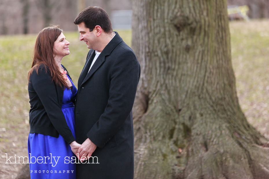 engaged couple in front of tree