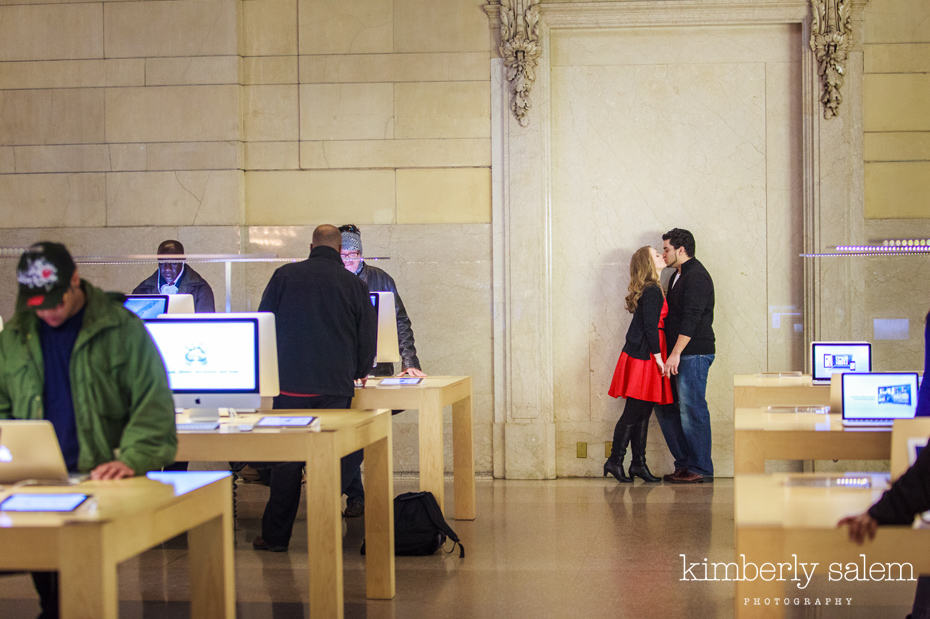 engaged couple kisses in the Grand Central apple store