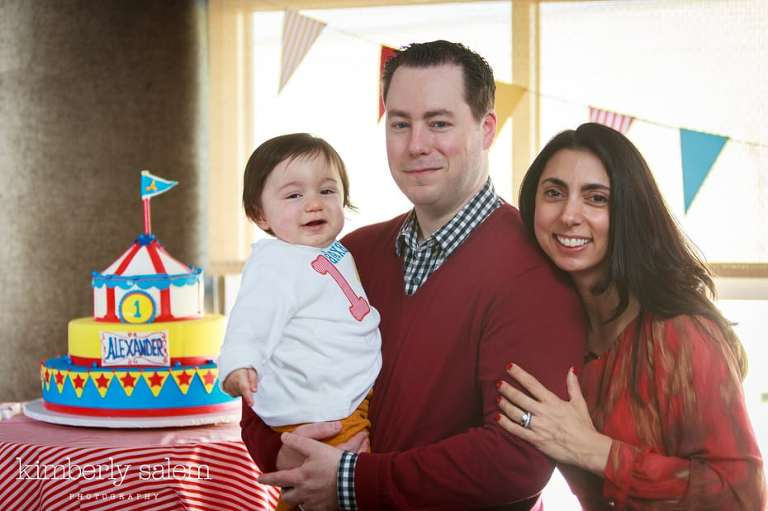 first birthday boy with his parents and cake in background