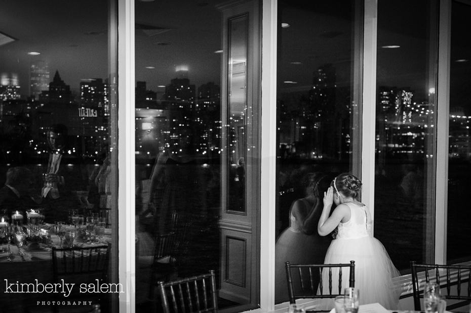 flower girl looks out window to Manhattan view - Water's Edge