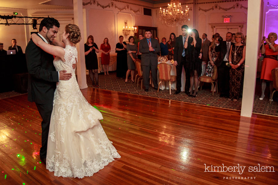 bride and groom dance while guests look on