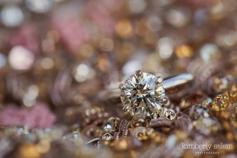 closeup of engagement ring with bridal gown as backdrop