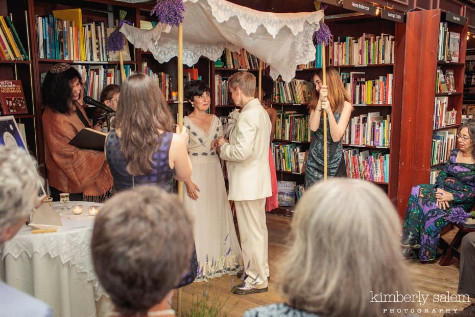 Brides getting married in bookstore under the chuppah