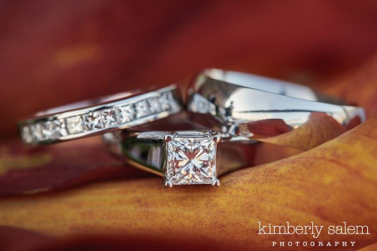 engagement ring and wedding rings together inside orange calla lily