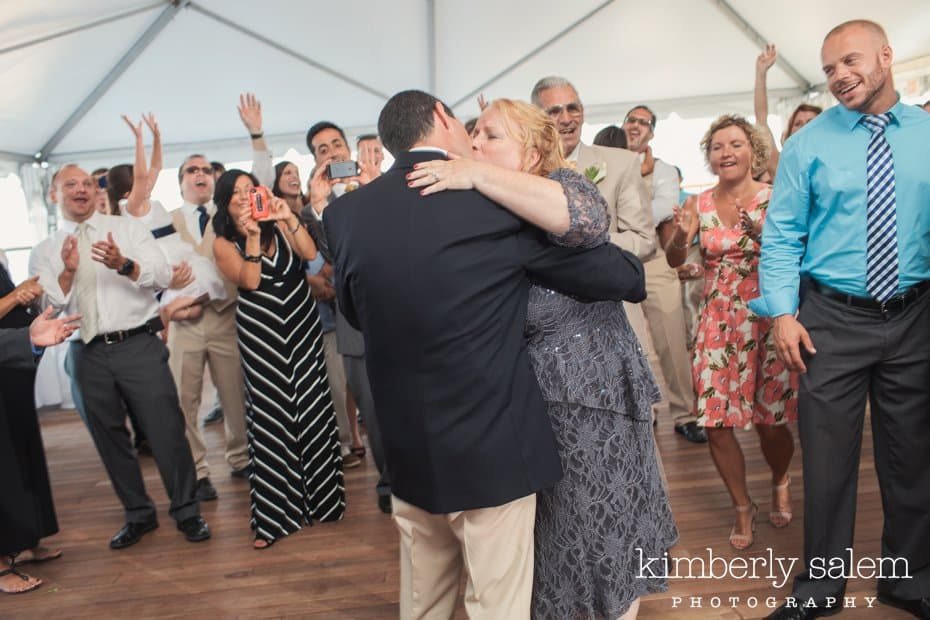 bride and groom kiss during first dance with guests looking on