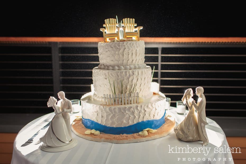 beach themed wedding cake with parents' cake toppers on either side