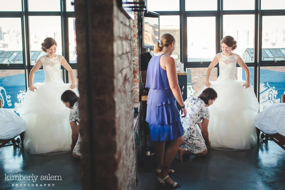Bride getting ready - maid of honor helping her dress