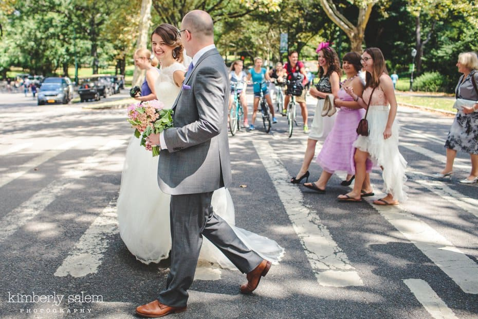 Bride, groom and wedding party walk across a crosswalk in Central Park