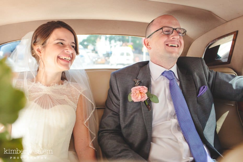 Bride and groom laugh inside Rolls Royce