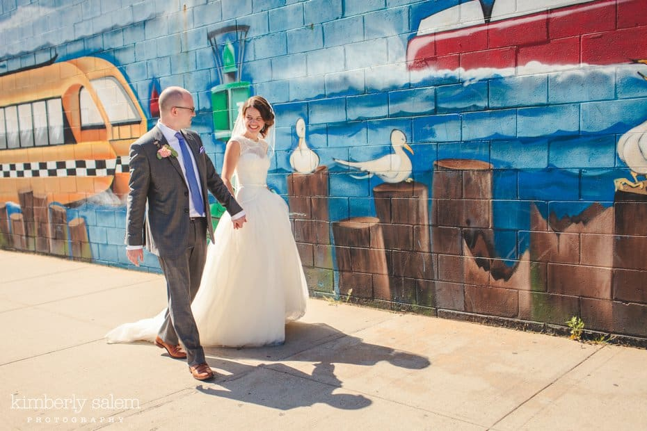 Bride and groom walk in front of a painted mural in Williamsburg, Brooklyn