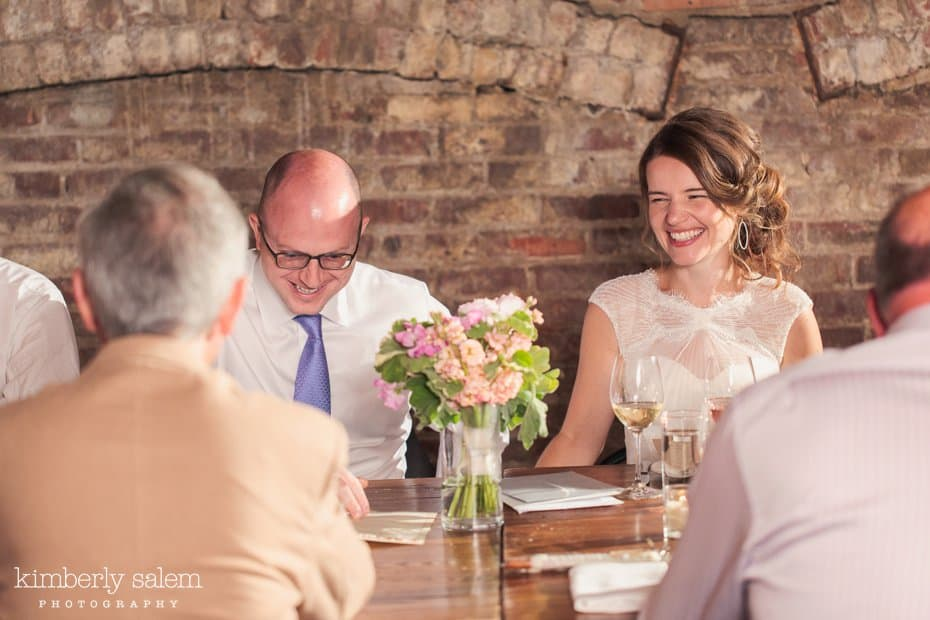 Groom and Bride laugh with guests at their dinner reception