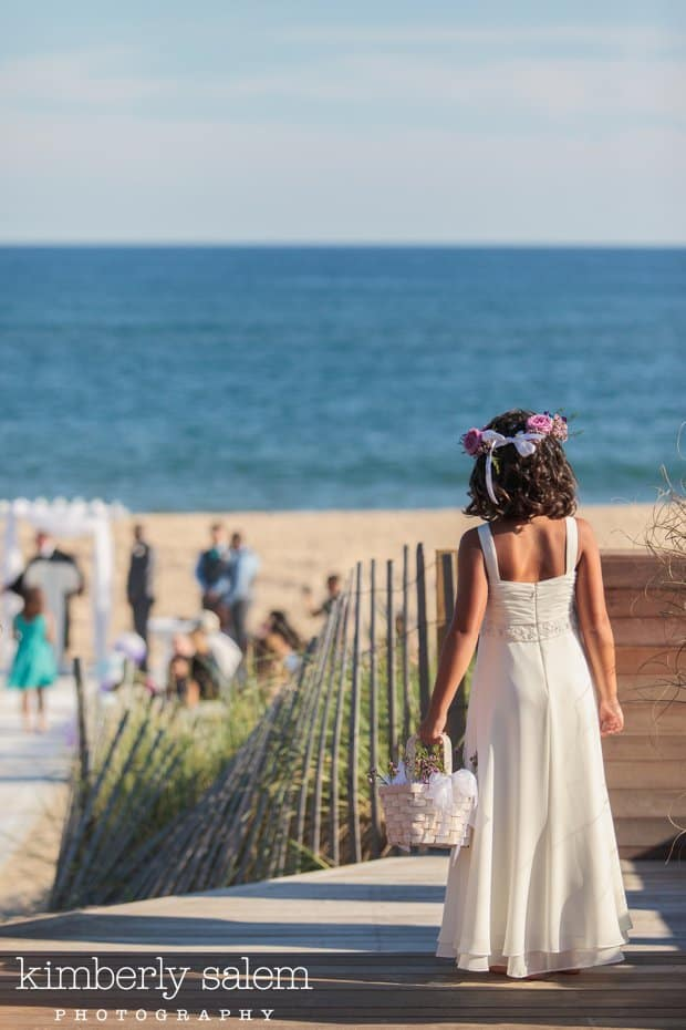 flower girl getting ready to walk down the aisle on the beach