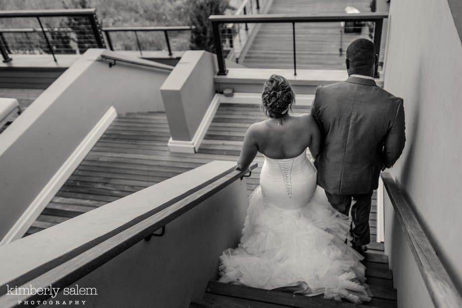 bride and groom walk down the winding stairs at Gurney